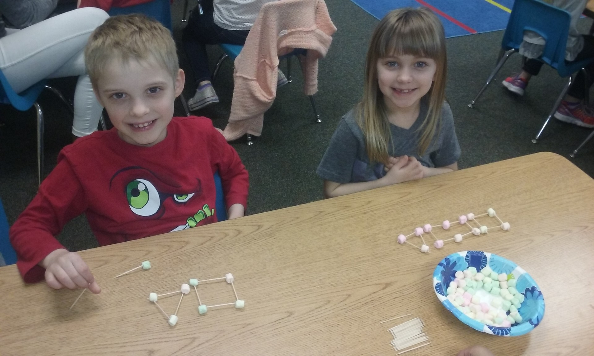 Two students build shapes with marshmallows and toothpicks