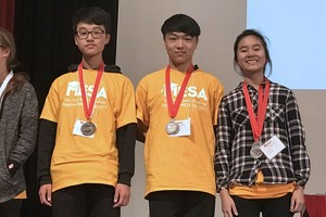 Three students with yellow shirts on stage with medals