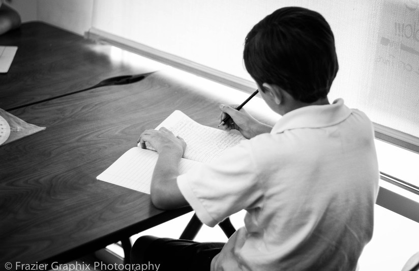 Student writing at his desk.