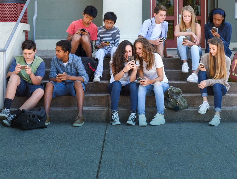 Teenagers viewing their cell phones on steps of school.