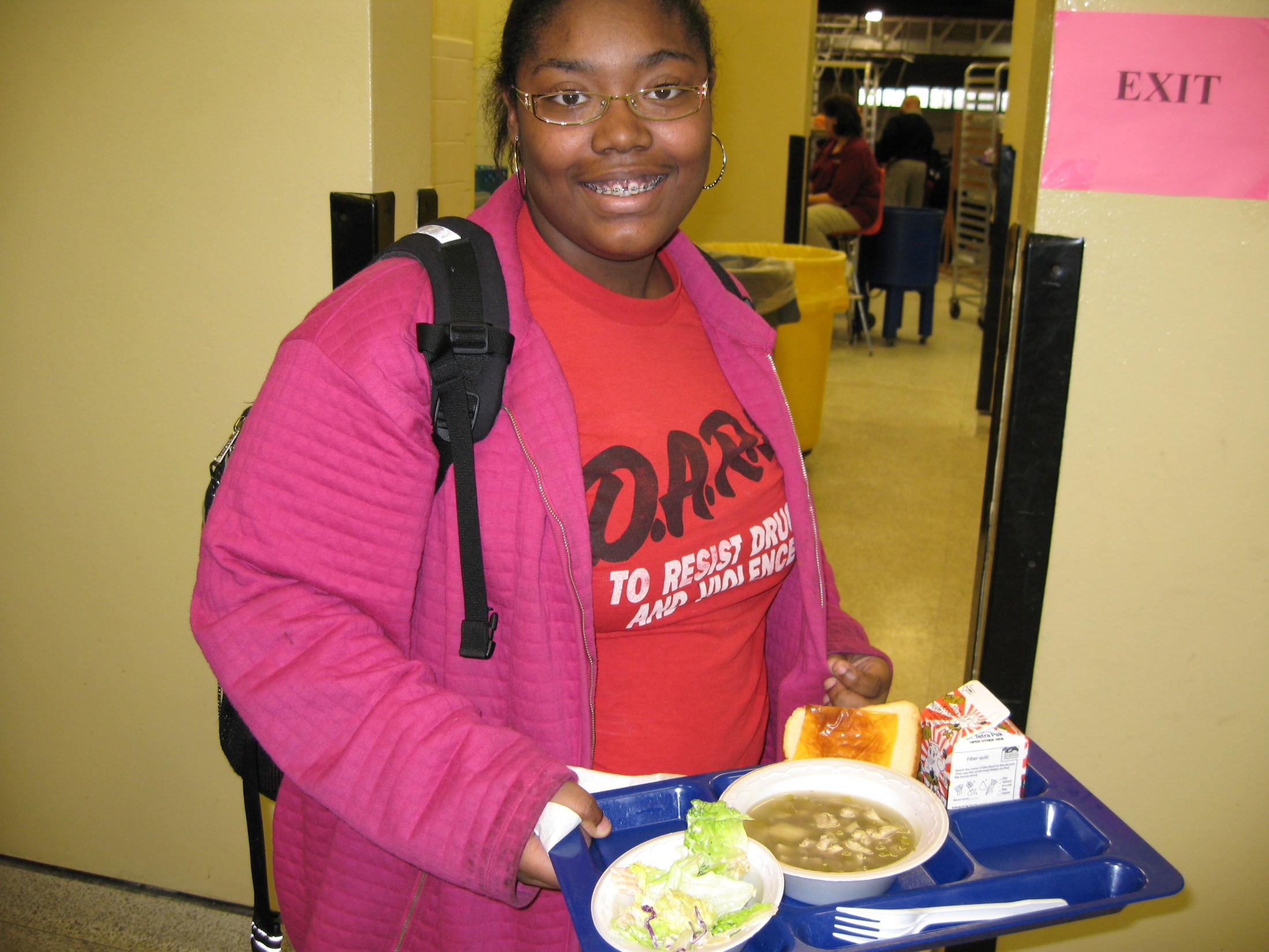 Student smiling holding lunch tray.