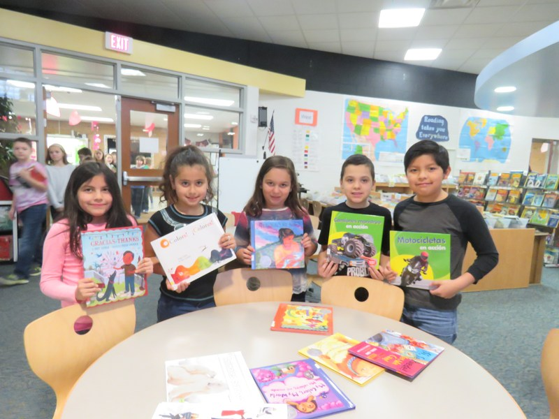 Lee students hold up some of the new books purchased written in Spanish and some in both Spanish and English.