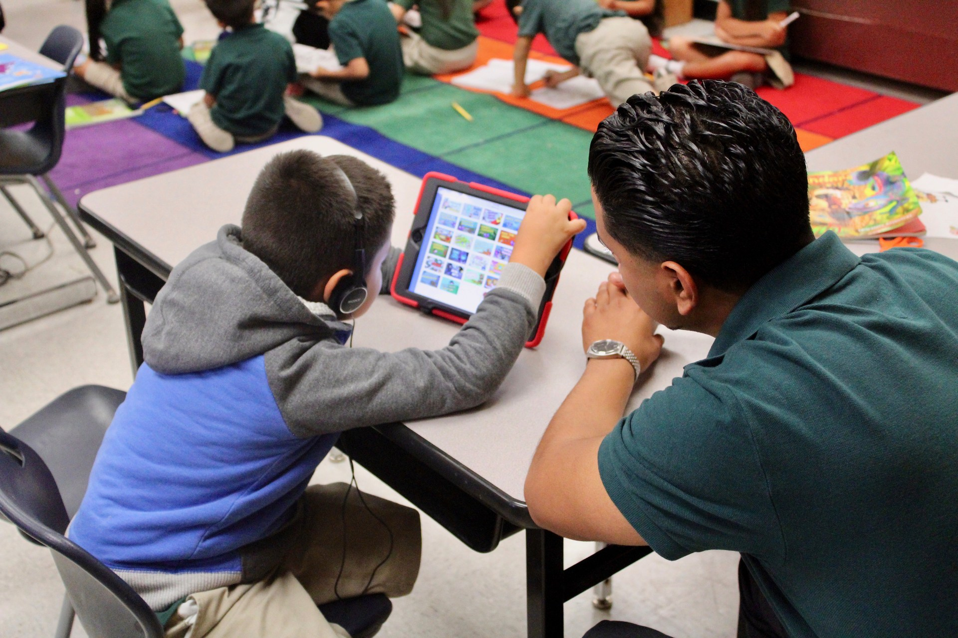 Tutor helps student with reading lesson on iPad