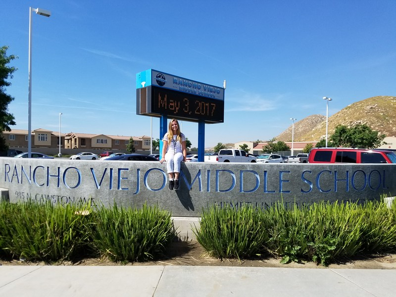 Chandler Kelly in front of a Rancho Viejo sign.