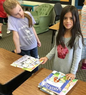 Second graders packing books for the Children's Book Bank
