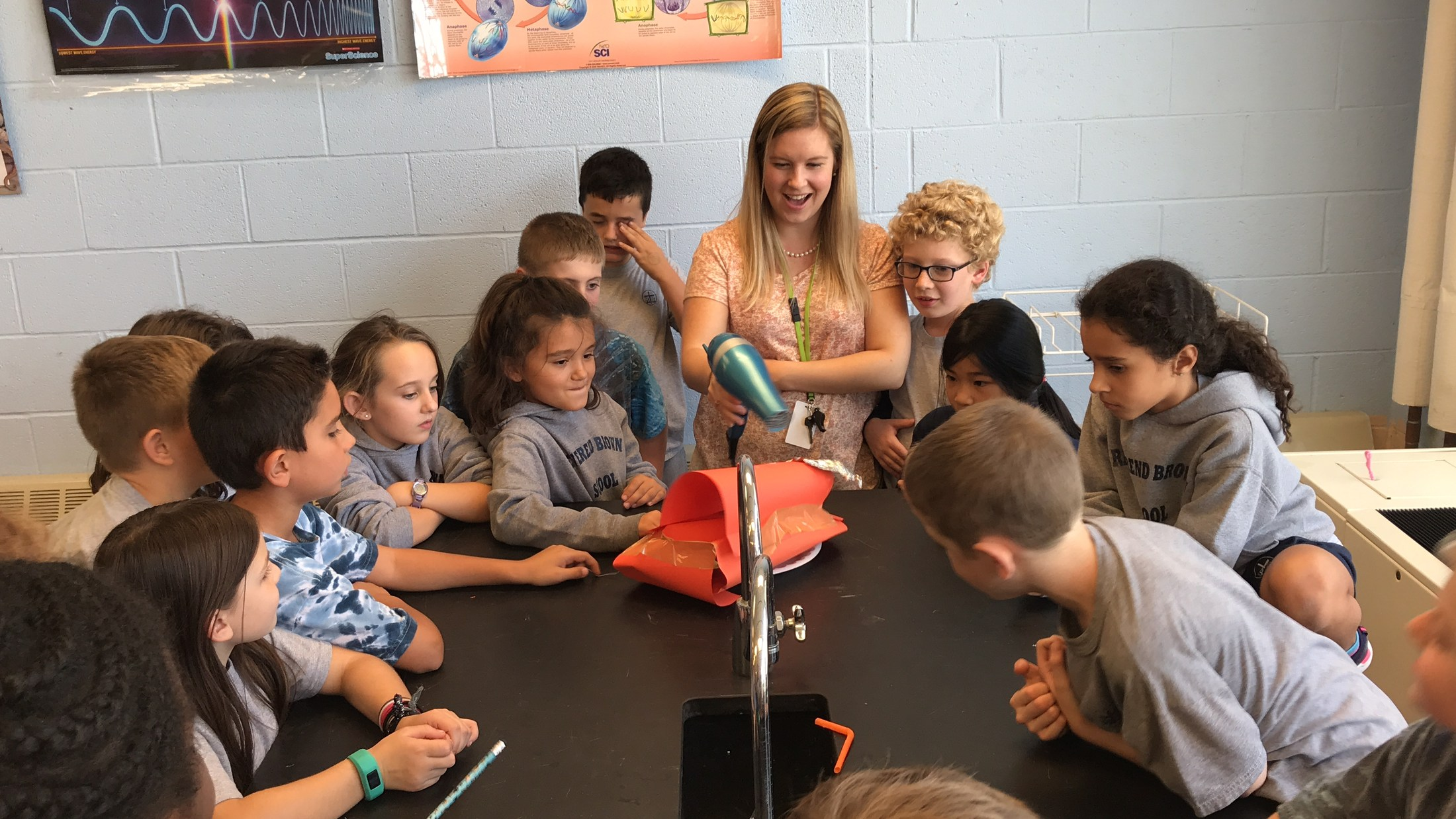 Students watch teacher use blow dryer during science experiment