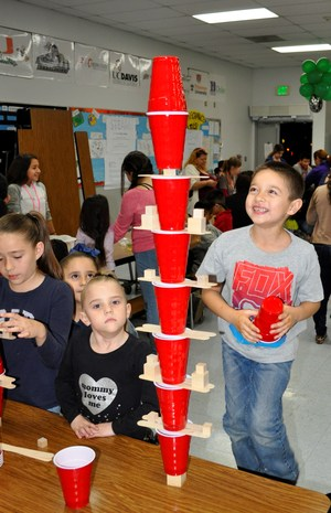 Foster Elementary School second-grader Keith Lang III stacks cups so high he can barely reach the top even standing on a bench during the school's first STEAM Night on Feb. 1.