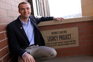 (1) Stewarts Creek grad Hunter Bullock poses in front of the plaque that marks his family's leadership with the Legacy Project, a brick-paver courtyard created at the entrance to the school.