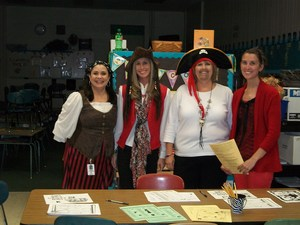 Four first grade teachers, dressed as pirates, are standing behind a table.