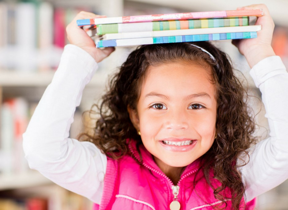 girl balancing books on head in library