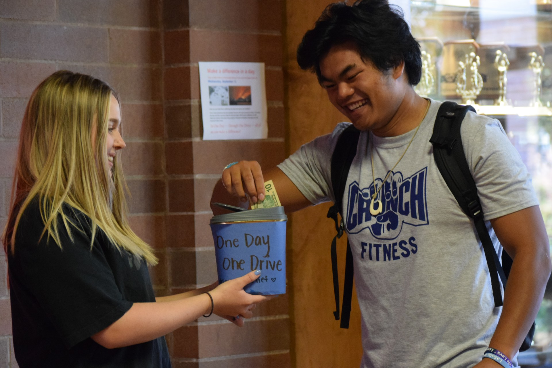Student putting donation in bucket.