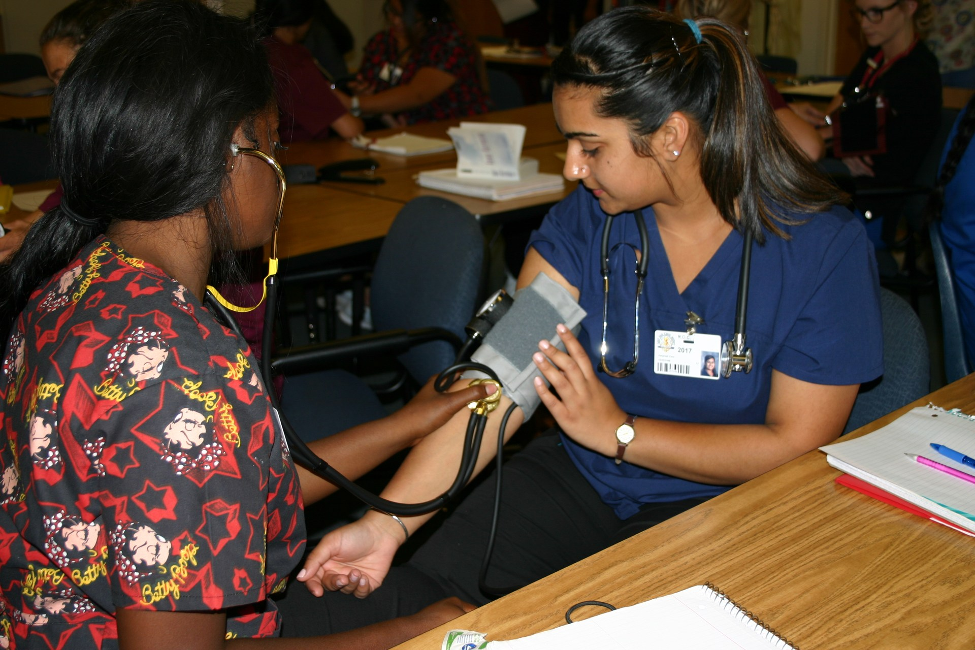 students taking blood pressure of another student in medical assistant class