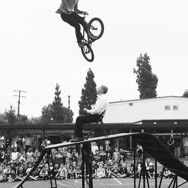 Dr. Blackwell sitting on a chair while a bike stuntman jumps over him