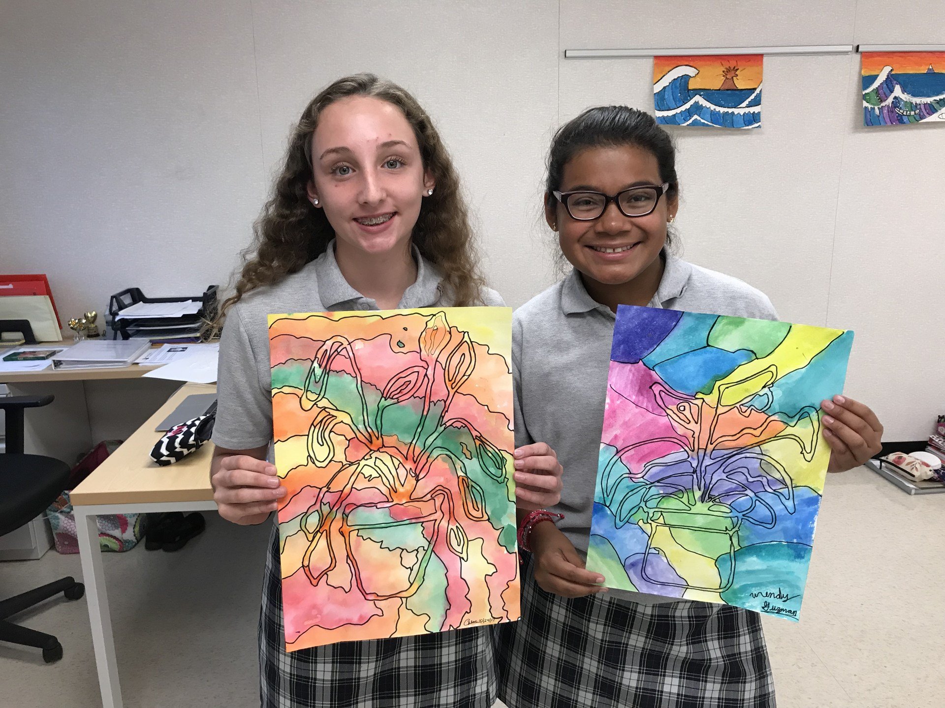 Two girl students pose for picture with drawings