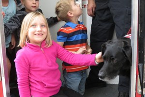 One of the students pets Jake the Fire Safety Dog as she walks out of the ESCAPE truck.