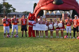 Coahoma football players and cheerleaders holding publicity check