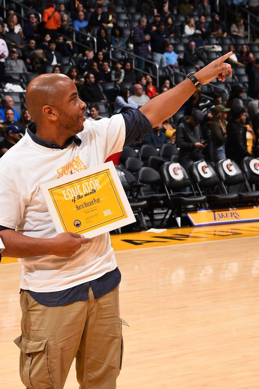 North Park High School Principal H. Vincent Pratt acknowledges a cheering section of colleagues at the Jan. 17 Lakers game where he was honored as an Educator of the Month.