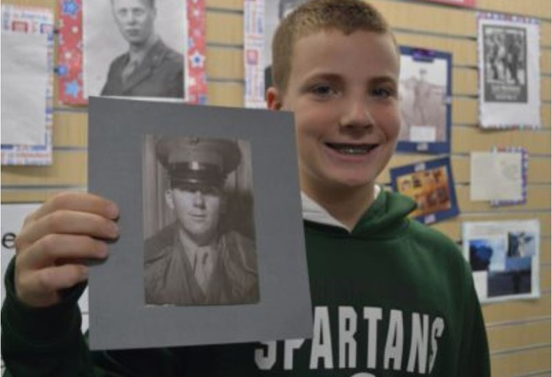 boy in Spartans sweatshirt holds up a black and white photo of a veteran in a hallway