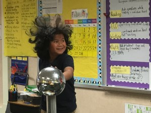 Boy's hair stands up on head when touching static electricity ball.