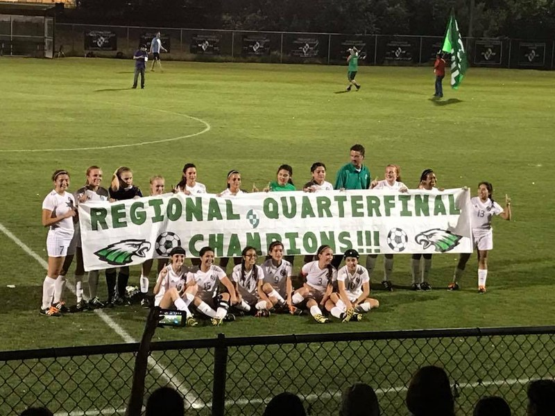 soccer team holding a sign