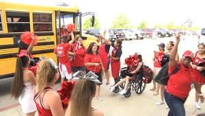 Teachers getting off the bus to cheers from Manor High School cheerleaders=