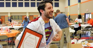 Smiling man holding plaque and showing his Superman shirt