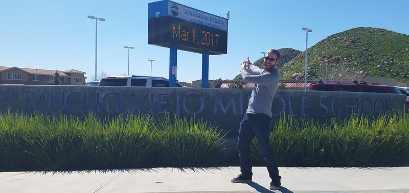 Corey Hanson in front of the Rancho Viejo Middle School sign.