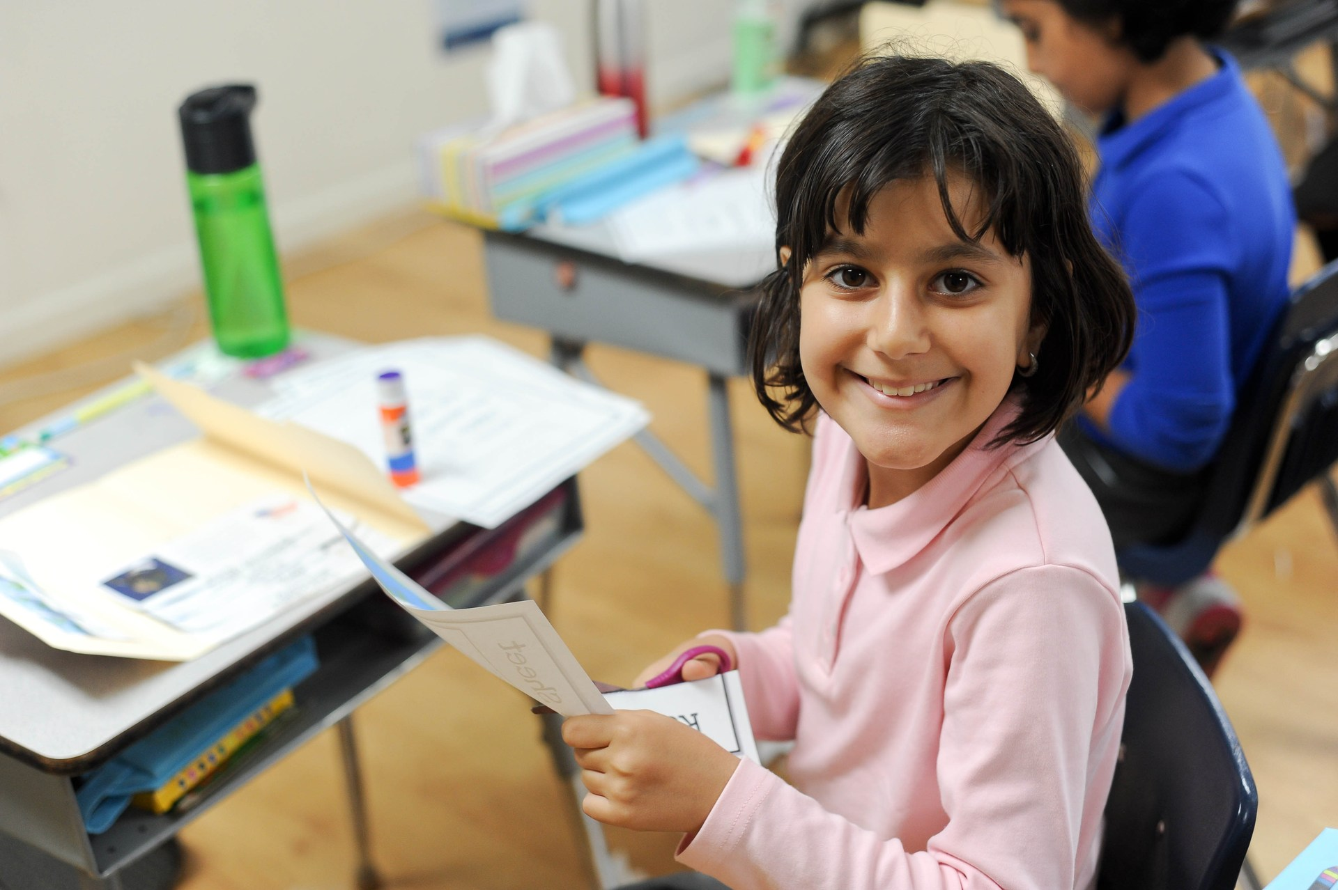 girl cutting a paper in classroom