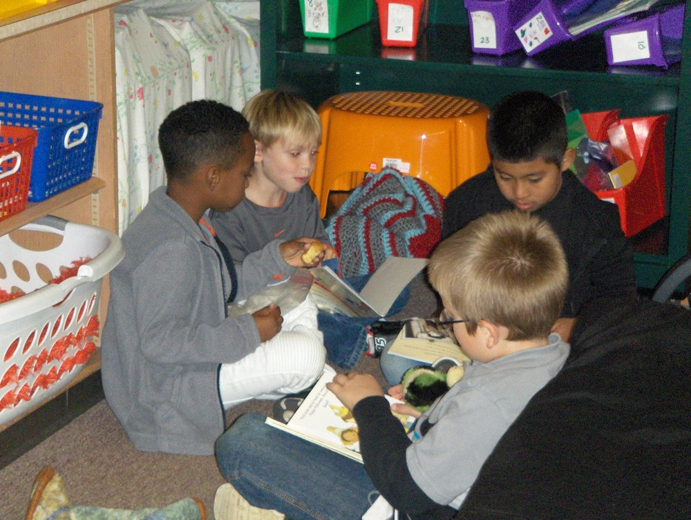 Four 1st grade boys enjoying books together in a classroom