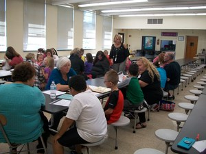 Parents and students are working together at the cafeteria tables.