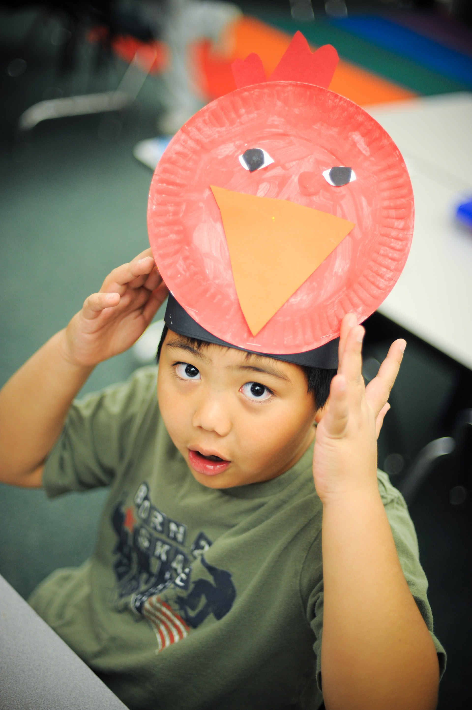 A boy showing his bird mask.