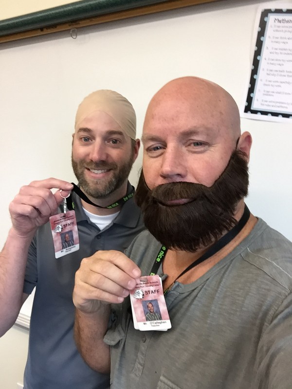 photo of man with fake beard and his friend with a bald cap, showing their id tags