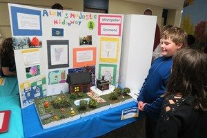 A student explains his project to another student.