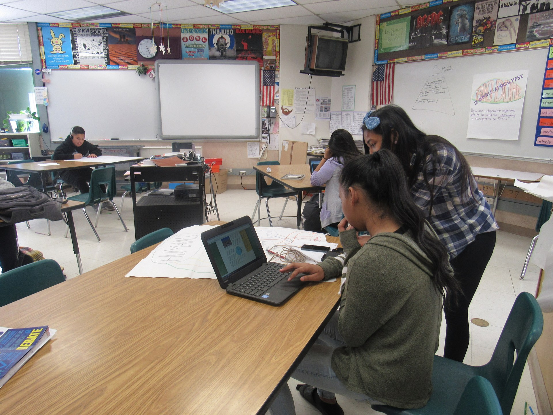 student seated at desk with a computer and a teacher standing next to the student