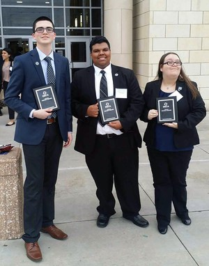 Three DECA students pose with district awards