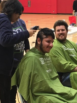 A student gets his head shaved while a teacher waits his turn.