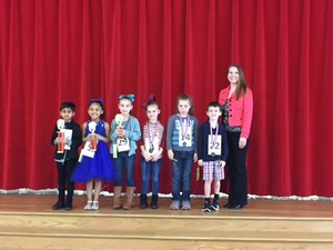 spelling bee winners first through sixth place pictured with their trophies and medals and the principal, Mrs. Fowler