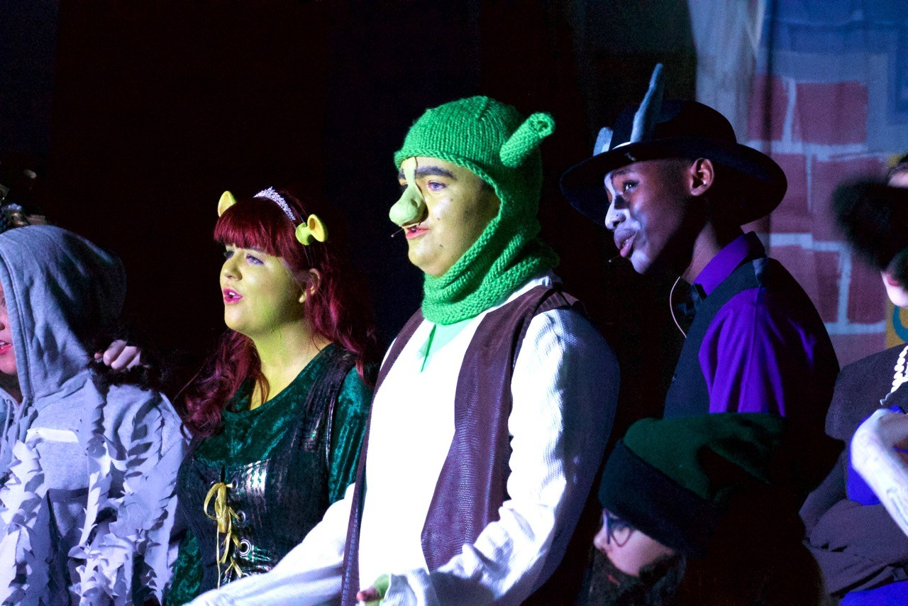 Students singing in Shrek costumes