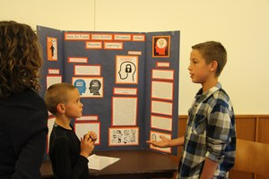 Student presents his project at the Great Brains Expo to another student.