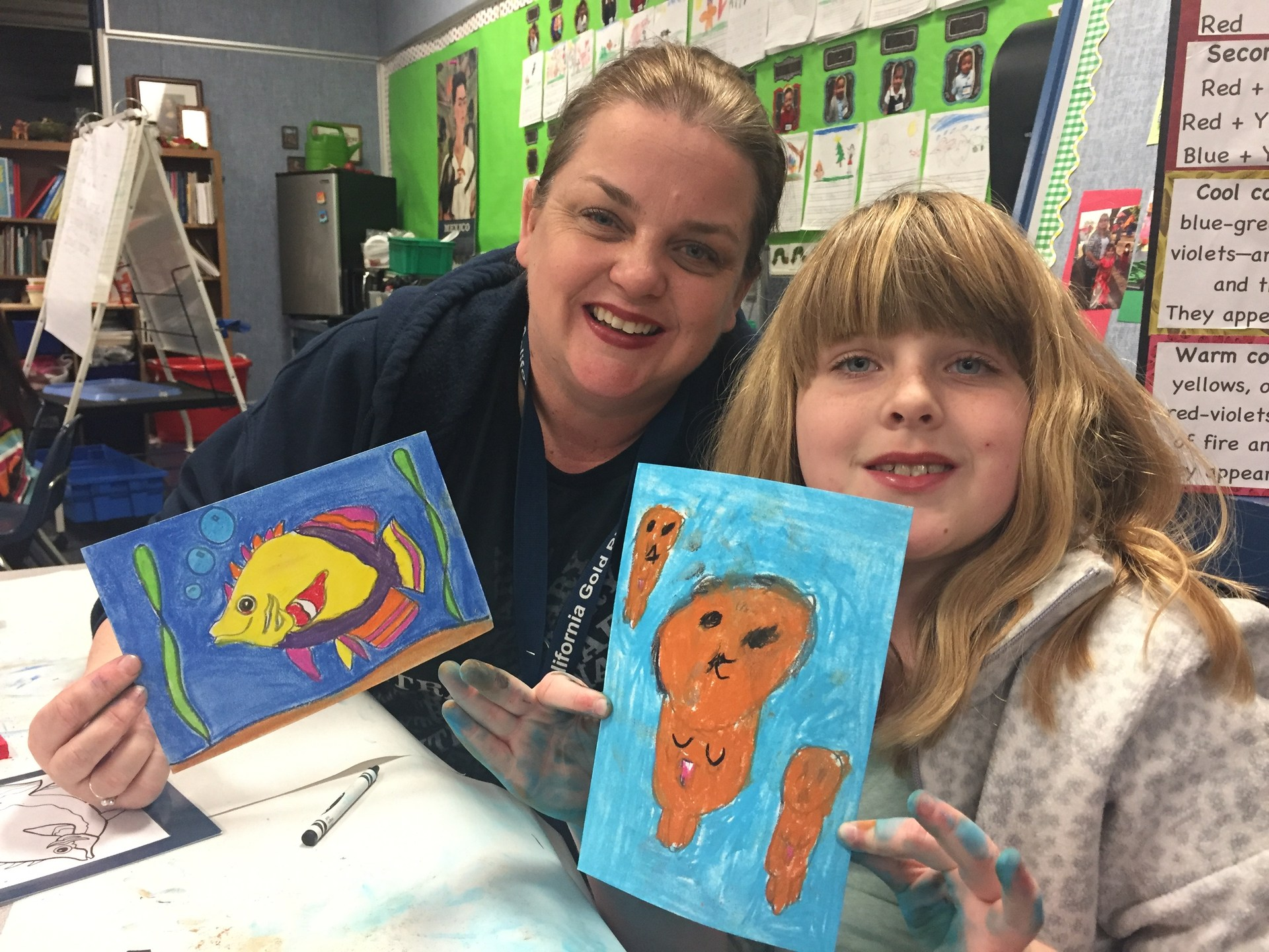 A mom and her daughter showing their drawings of a fish.