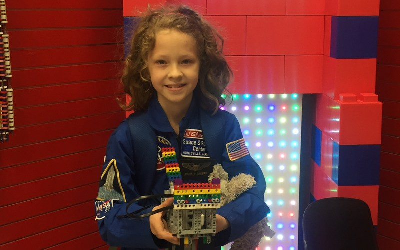 Katie is holding a robot that she helped build while at space camp.
