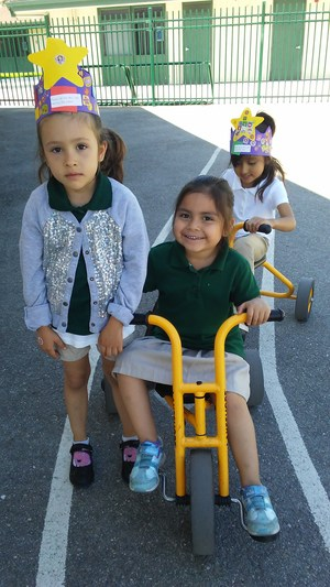 3 kindergarteners riding trikes and playing on the playground