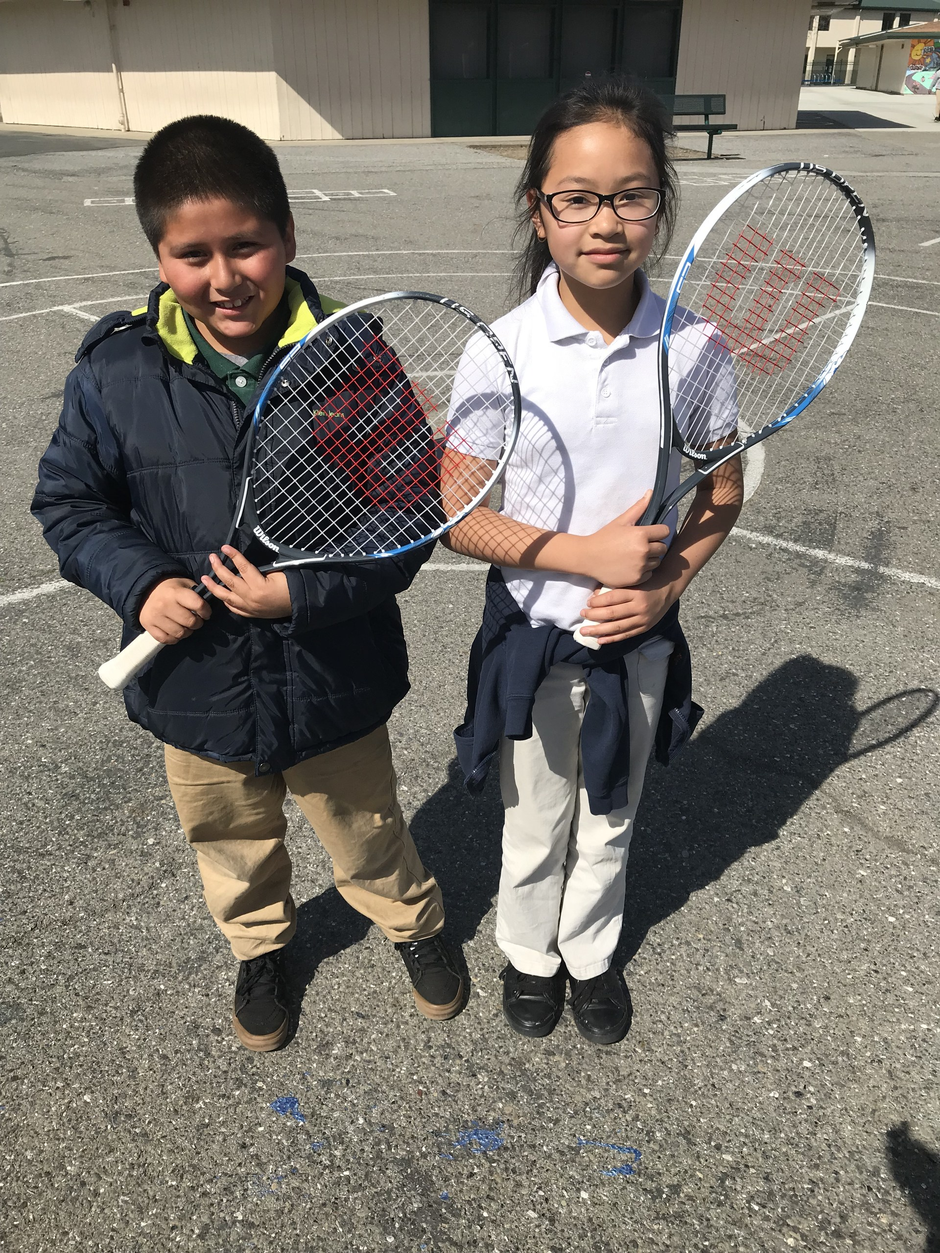 students with tennis rackets