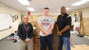 Chief Aguirre, Andrew Weishaar, and Chief Warrant Officer Alfonza Walton in front of the donation boxes collected.