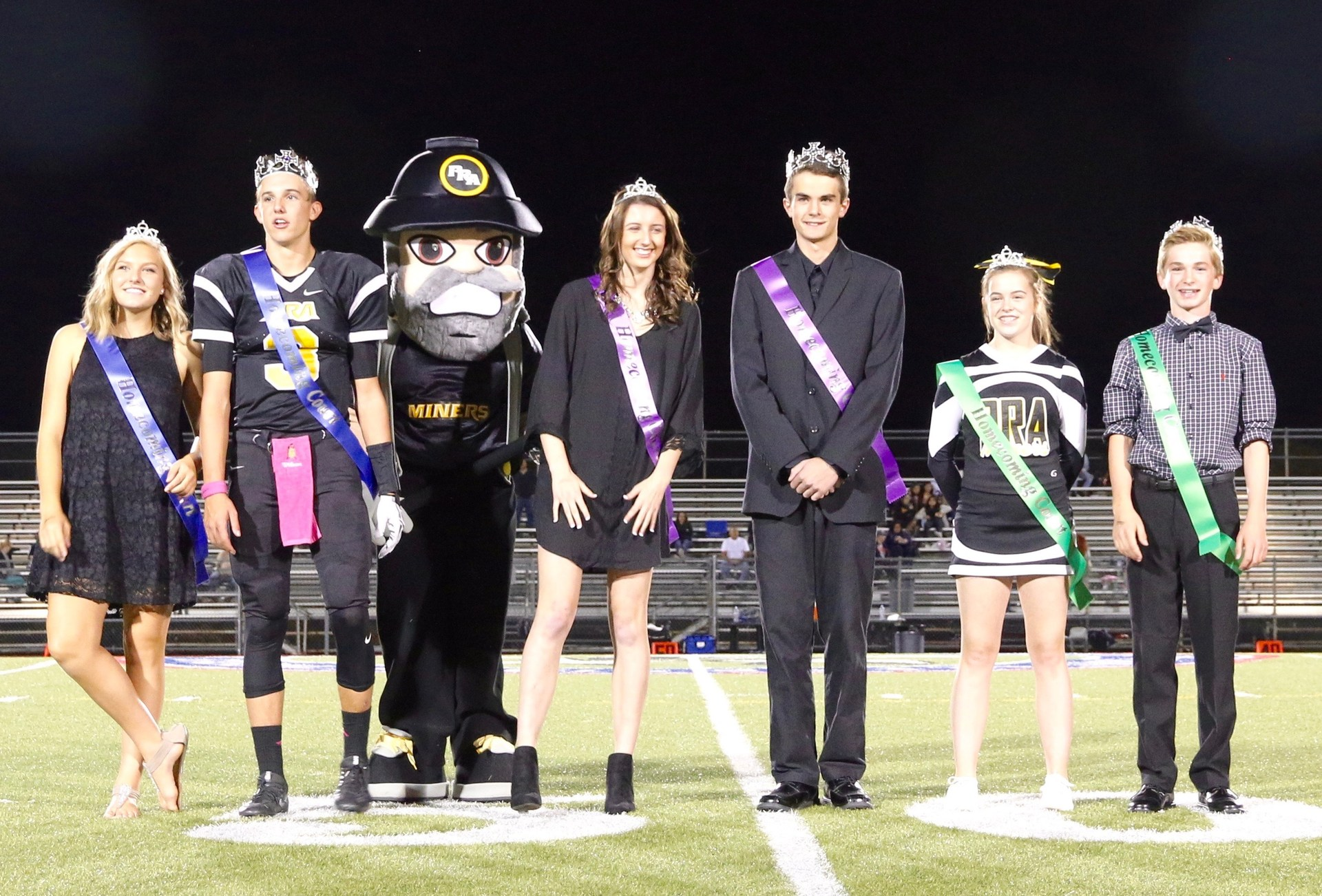 student homecoming royalty posing with school Miner mascot