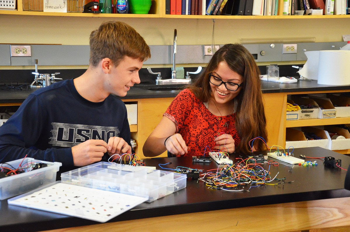 Upper school students work together with electronics in science class
