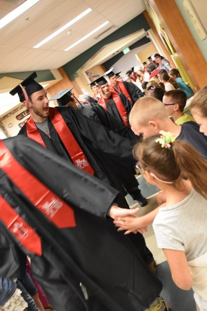 Seniors giving high-fives to students lining the halls of Moxee Elementary.