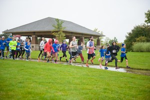 adults and children running 5K in rain with pavilion in background