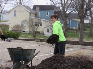 A student fills a wheelbarrow with mulch to put around the flower beds and lanscaping at the fire station.