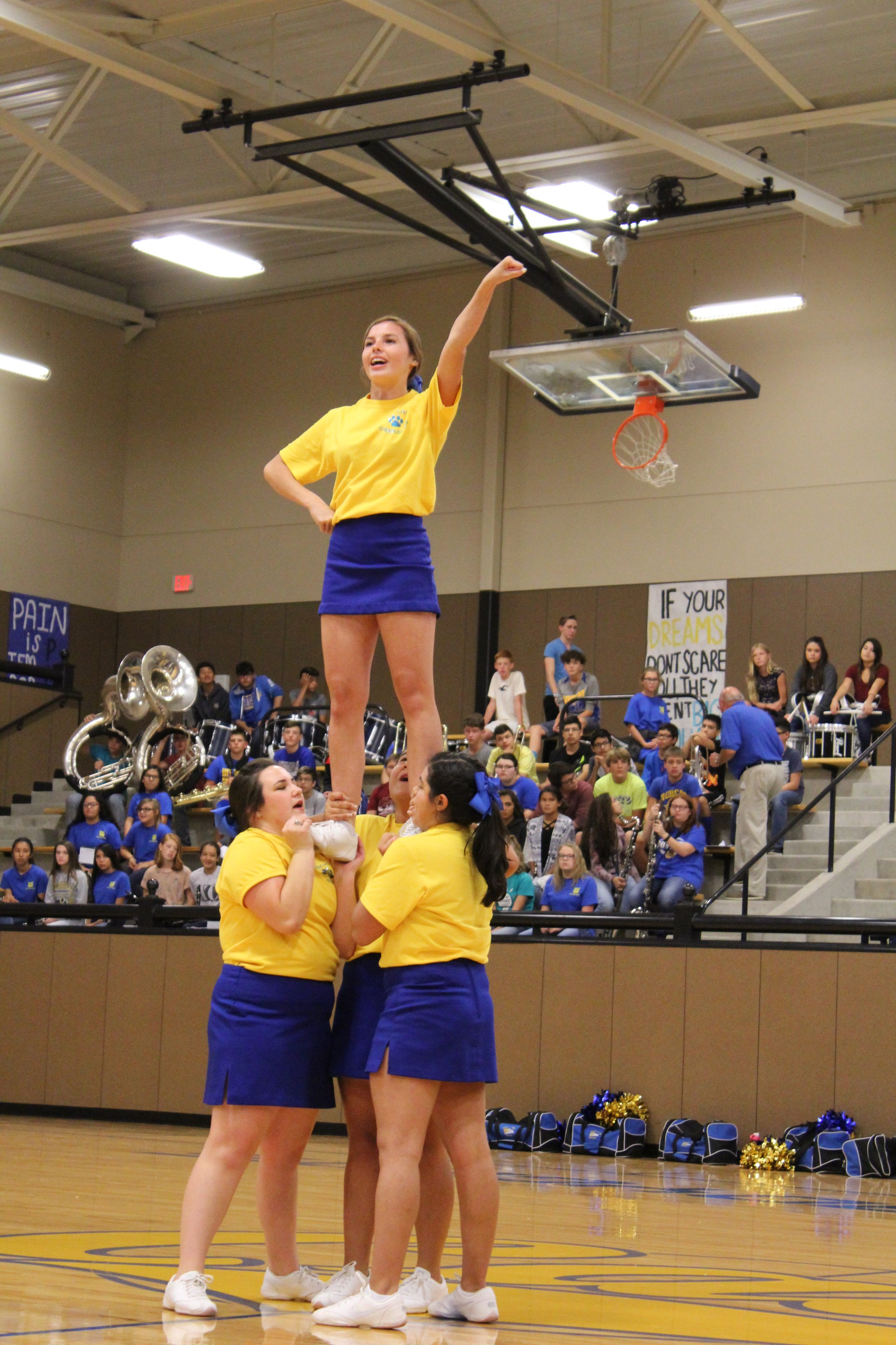 Varsity Cheerleaders Cheering on Bobcats with a Stunt